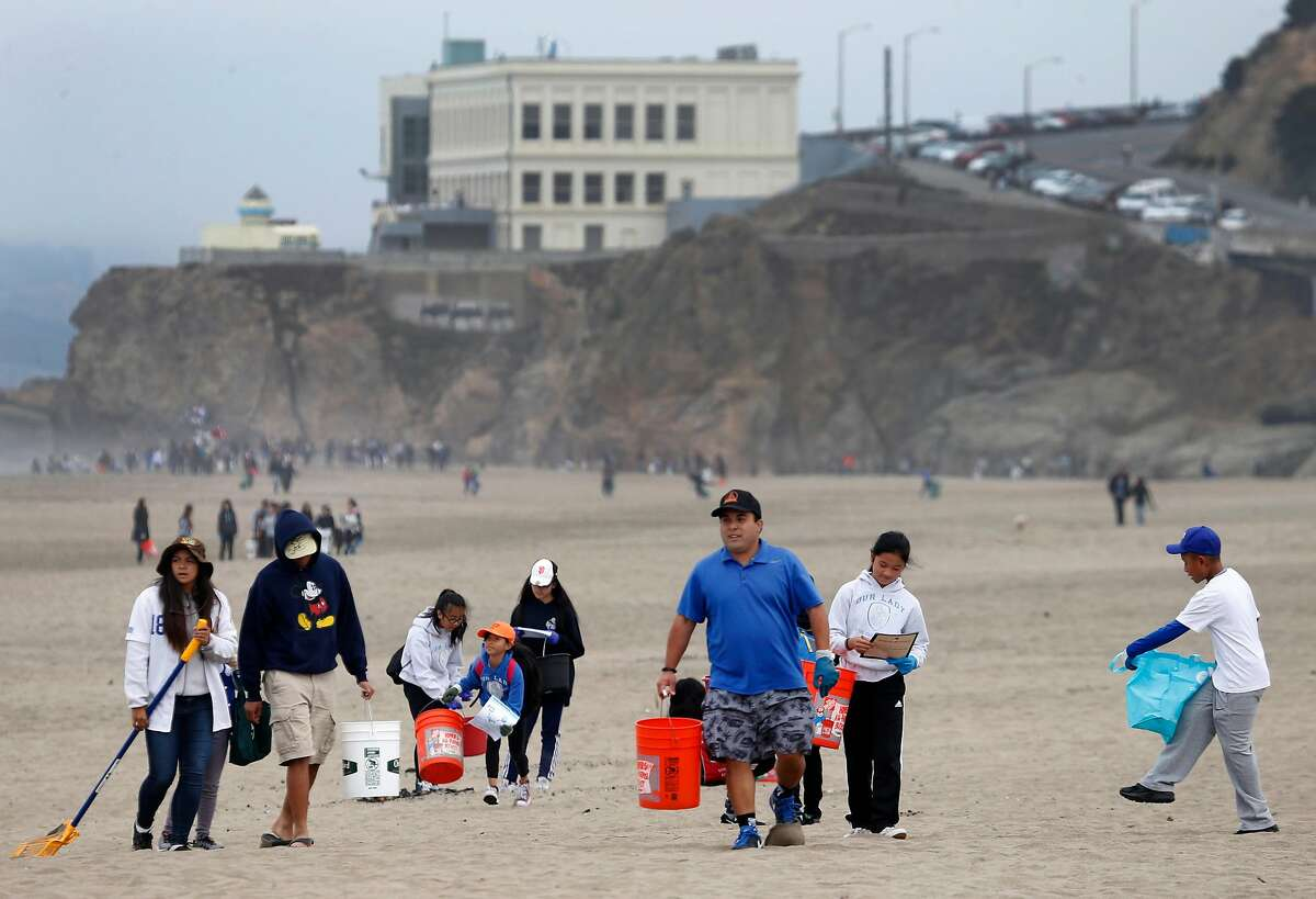 A youth group picks up trash on Ocean Beach in front of the Cliff House as hundreds of volunteers participate in the annual California coastal cleanup in San Francisco, Calif. on Saturday, Sept. 17, 2016.