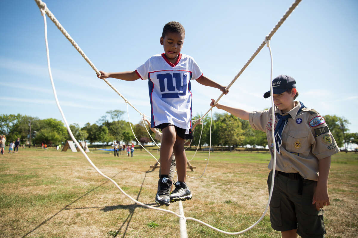 Elijah Fitchett, 6, concentrates on crossing a rope bridge with help from Joey Rosario during the second annual Norwalk Scouting Adventure at Taylor Farm in Norwalk on Saturday.