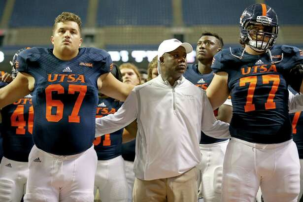 UTSA guard Kyle McKinney (from left), head coach Frank Wilson, Zach Pare, and others stand during the school song after the game with Arizona State on Sept. 16, 2016 at the Alamodome. The Sun Devils won 32-28.