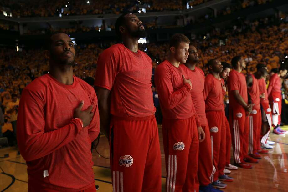 Members of the Los Angeles Clippers listen to the national anthem before Game 4 of an opening-round NBA basketball playoff series against the Golden State Warriors on Sunday, April 27, 2014, in Oakland, Calif. The Clippers chose not to speak publicly about owner Donald Sterling. Instead, they made a silent protest. The players wore their red Clippers' warmup shirts inside out to hide the team's logo. (AP Photo/Marcio Jose Sanchez) Photo: Marcio Jose Sanchez, Associated Press