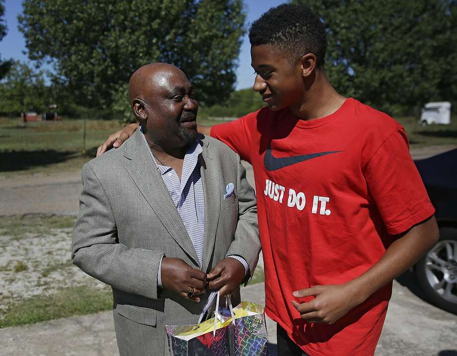 Dwight Beal,14, hugs Rev. Joey Crutcher whose son Terence Crutcher was shot and killed by Tulsa Police Friday night Sept. 17, 2016. Joey Crutcher attended an event that he helped organize called Men's Encounter. The event was held to mentor  African American men and help them become successful. It also taught how do interact with police if they were to come in contact with them. Beal, who attends church with Crutcher, wanted to check on him becuase his son had been shot and killed by Tulsa Police the night before. (Mike Simons/Tulsa World via AP) Photo: Mike Simons, Associated Press