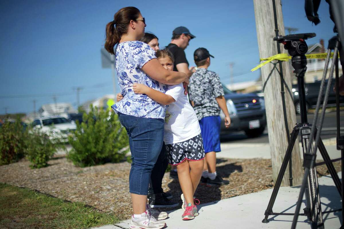 SEASIDE PARK, NJ - SEPTEMBER 17: Mother and daughter, Audrey King, 46, and Alina, 8, embrace near the scene of an