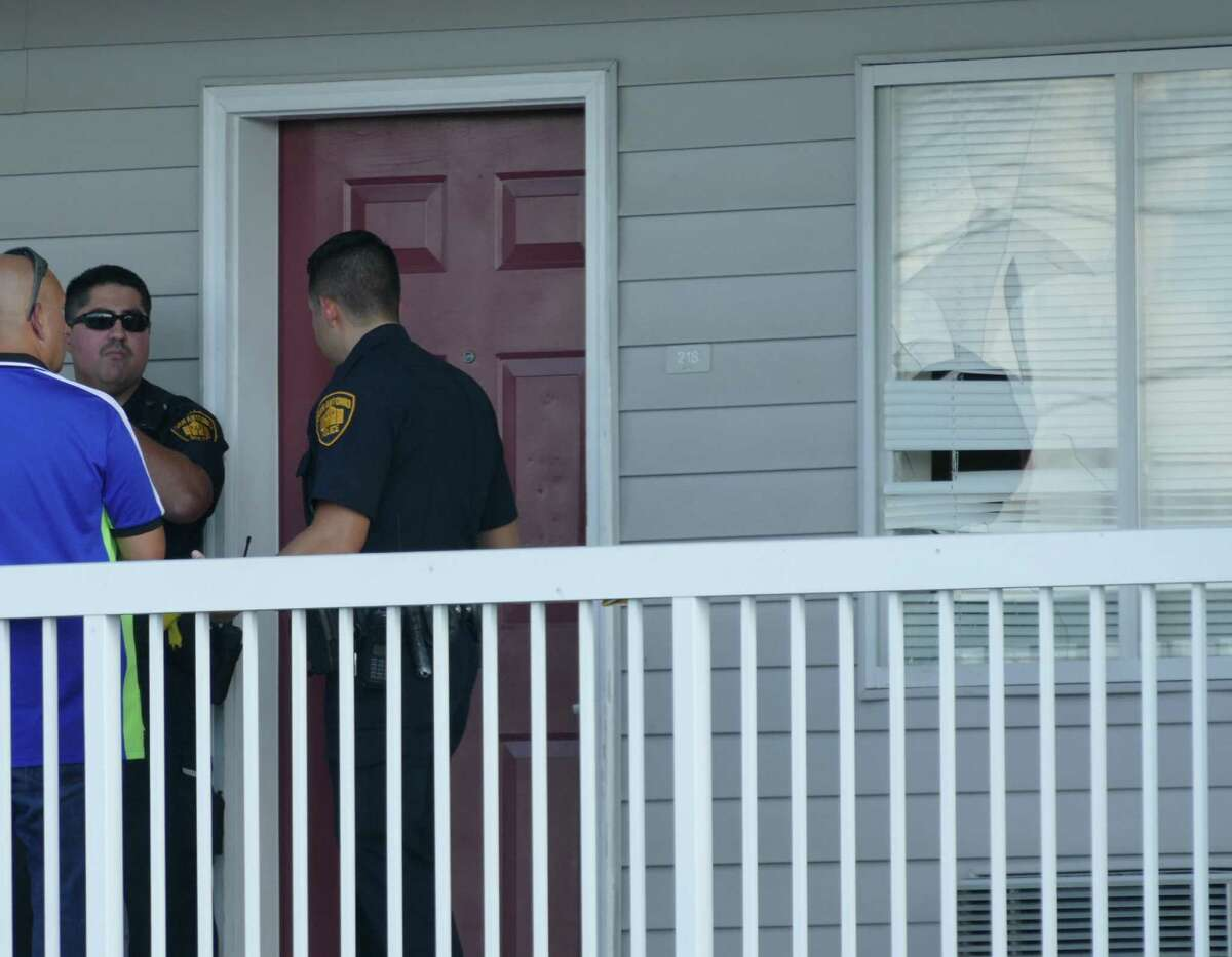 Police investigate the scene at a motel in the 7400 block of Culebra Road where man was shot after a confrontation between him and another tenant of the motel on Saturday, Sept. 17, 2016. The door appears to show damage by a broken window.