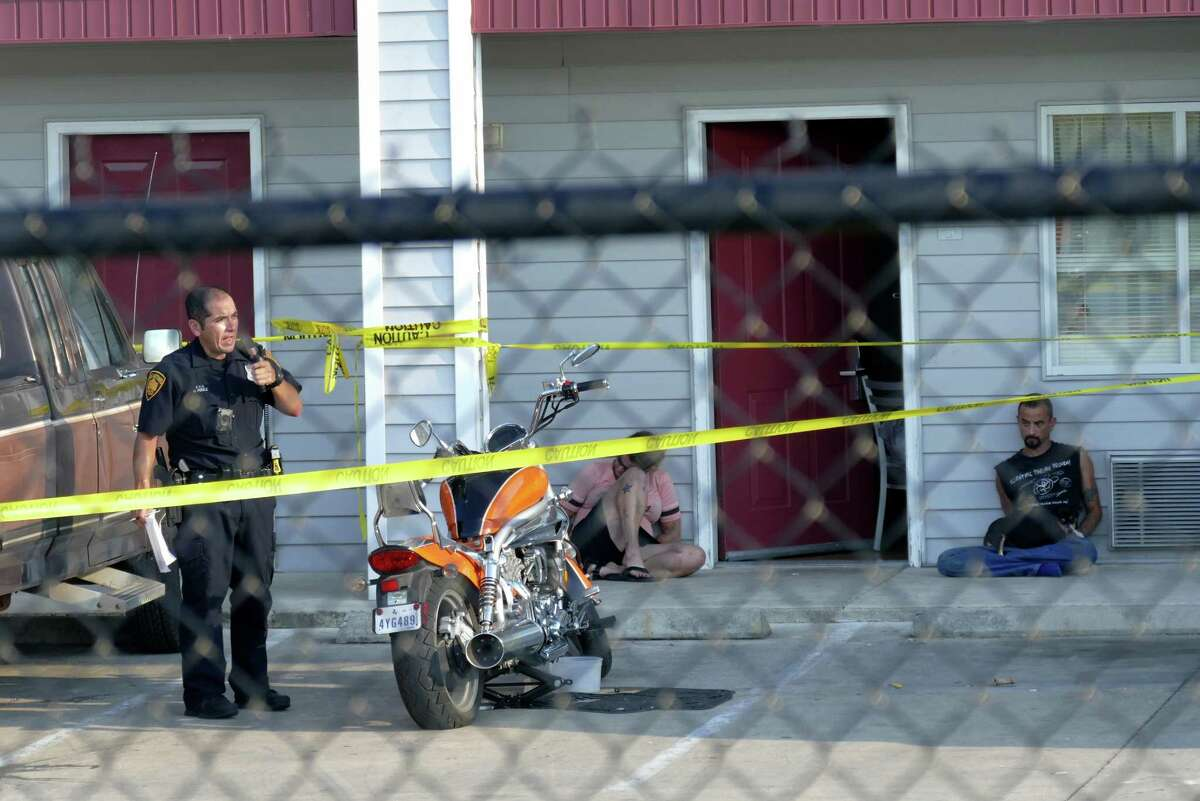 Two people are handcuffed by the scene where a man was shot after a confrontation at a motel in the 7400 block of Culebra on Saturday, Sept. 17, 2016.