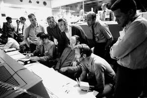 """S70-34986 (NASA Caption) """"A group of eight astronauts and flight controllers monitor the console activity in the Mission Operations Control Room (MOCR) of the Mission Control Center (MCC) during the Apollo 13 lunar landing mission. Seated, left to right, are MOCR Guidance Officer Raymond F. Teague; Astronaut Edgar D. Mitchell, and Astronaut Alan B. Shepard Jr., Standing, left to right, are Scientist-Astronaut Anthony W. England; Astronaut Joe H. Engle; Astronaut Eugene A. Cernan; Astronaut Ronald E. Evans; and M.P. Frank, a flight controller. When this picture was made, the Apollo 13 moon landing had already been cancelled, and the Apollo 13 crewmen were in transearth trajectory attempting to bring their crippled spacecraft back home."""" Mitchell and Shepard, along with Stu Roosa, are the Apollo 14 Prime Crew and Cernan, Evans, and Engle the Apollo 14 Back-up Crew. Tony England was to have been the Apollo 13 EVA CapCom. April 13, 1970."""
