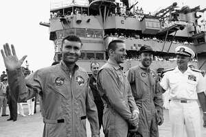Astronauts Fred Haise, left, Jack Swigert and Jim Lovell are wel- comed aboard the U.S. Iwo Jima by Rear Admiral Donald C. Davis.