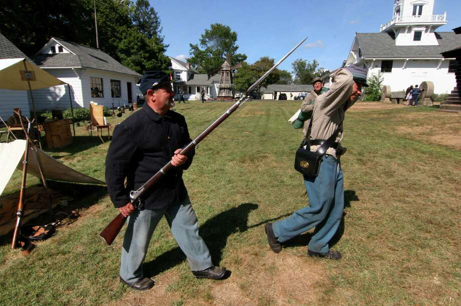 Company F, 14th Connecticut Volunteer Infantry soldier Mike Adiletta, of Seymour, takes a Confederate prisoner away (played by his son Joe, 18) during a Civil War reenactment and encampment held at Boothe Memorial Park in Stratford, Conn., on Saturday Sept. 17, 2016. This dedicated group of men and women set up camp on the park grounds the way it was done during the 1860s. Some of the highlights included military presentations and drills, firing demonstrations, a surgeon's tent and Civil War era weapons on display. Photo: Christian Abraham / Hearst Connecticut Media / Connecticut Post