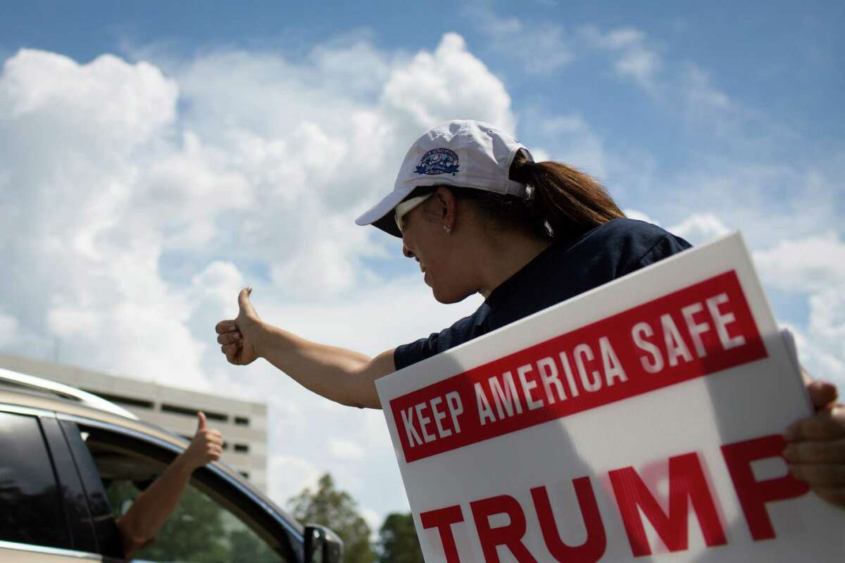 Emely McHattie gives the thumbs up to another Donald Trump supporter outside the Houston Omni Hotel at Westside Houston Saturday.