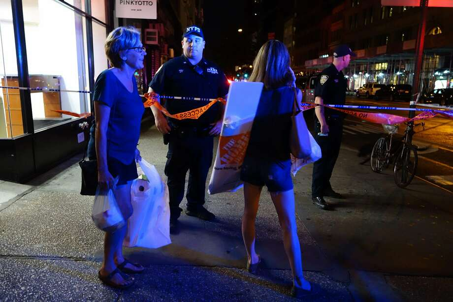 Two woman look on as police block a road after an explosion in New York on September 17, 2016.             An explosion in New York's Chelsea neighborhood injured multiple people Saturday night, police said. / AFP PHOTO / William EDWARDSWILLIAM EDWARDS/AFP/Getty Images Photo: WILLIAM EDWARDS, AFP/Getty Images