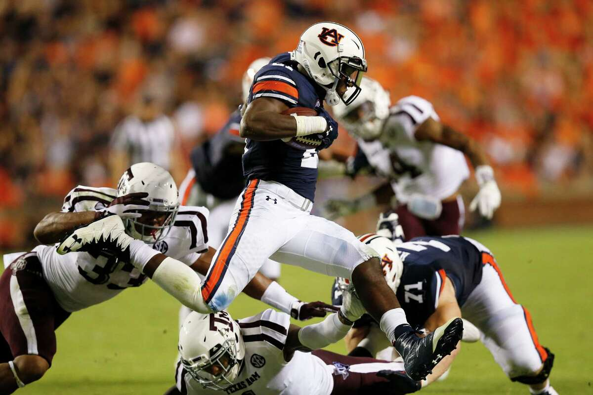 Auburn running back Kerryon Johnson leaps over Texas A&M defensive back Nick Harvey in the second half during an NCAA college football game, Saturday, Sept. 17, 2016, in Auburn, Ala. (AP Photo/Brynn Anderson)