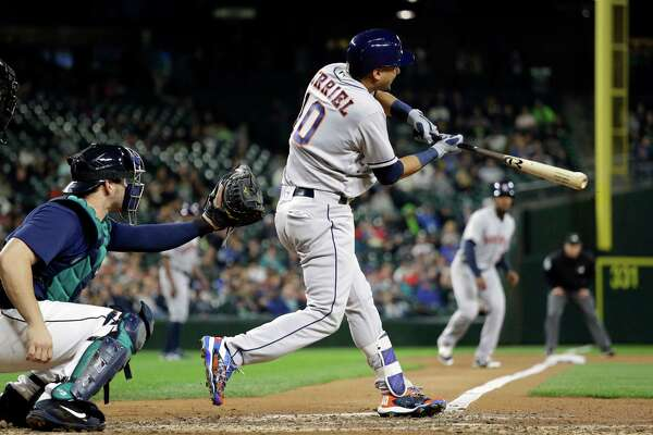 Houston Astros' Yulieski Gurriel singles in a pair of runs as Seattle Mariners cacher Mike Zunino watches during the sixth inning of a baseball game Saturday, Sept. 17, 2016, in Seattle. (AP Photo/Elaine Thompson)