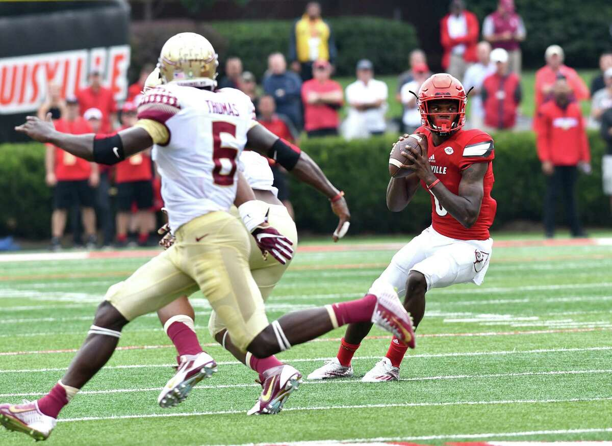 Louisville's Lamar Jackon (8) looks for an open receiver while avoiding the defense of Florida State's Matthew Thomas (6) in the first quarter of an NCAA college football game, Saturday, Sep. 17, 2016 in Louisville Ky. (AP Photo/Timothy D. Easley) ORG XMIT: KYTE103