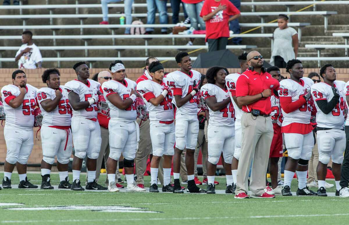 Alief Taylor Lions head coach Brian Randle and the team stand for the National Anthem during the high school football game between Alief Taylor Lions and the Seven Lakes Spartans at Rhodes Stadium in Katy, TX on Saturday, September 17, 2016. The Lions defeated the Spartans 44-3 at halftime.