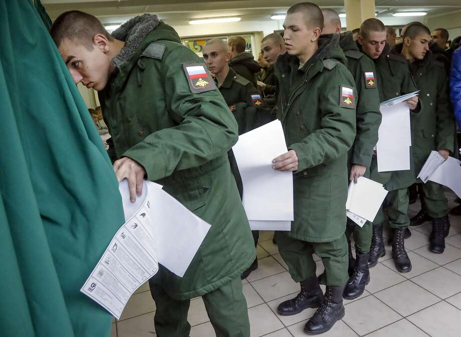 Army soldiers vote in parliamentary elections at a polling station outside St. Petersburg, Russia. Photo: Dmitri Lovetsky, Associated Press