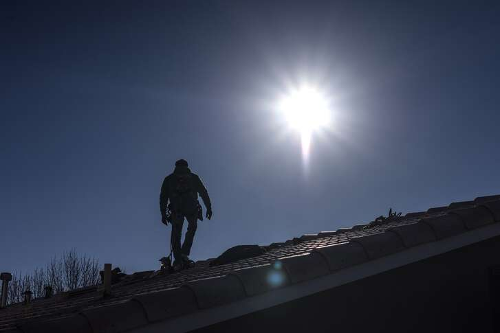 A worker walks on a roof during a SolarCity residential installation in Albuquerque, New Mexico, on Feb. 8, 2016. (MUST CREDIT: Bloomberg photo by Sergio Flores)