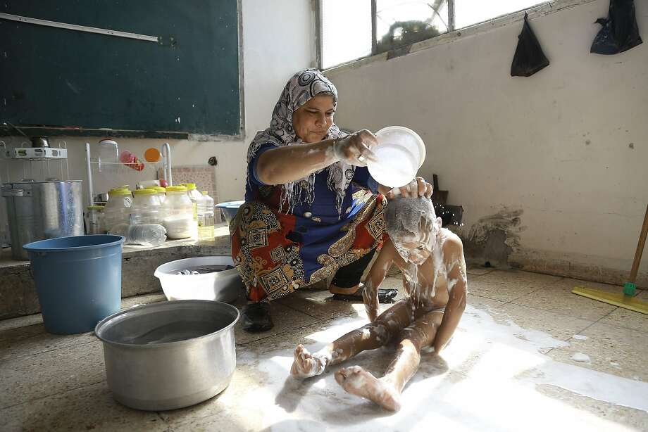 A Syrian woman bathes her child Friday at a school used as shelter by displaced families fleeing the Islamic State group in the Kurdish-majority northeastern city of Qamishli. Photo: DELIL SOULEIMAN, AFP/Getty Images