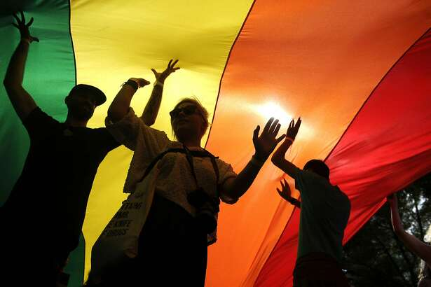 People take part in the Gay Pride parade under a huge rainbow flag, in Belgrade on September 18, 2016.  The Belgrade Gay Pride parade, the third in a row since the event was marred by violence in 2010, was held without incidents amid tight security as thousands of riot police officers were deployed in the city center. / AFP PHOTO / Oliver BUNICOLIVER BUNIC/AFP/Getty Images