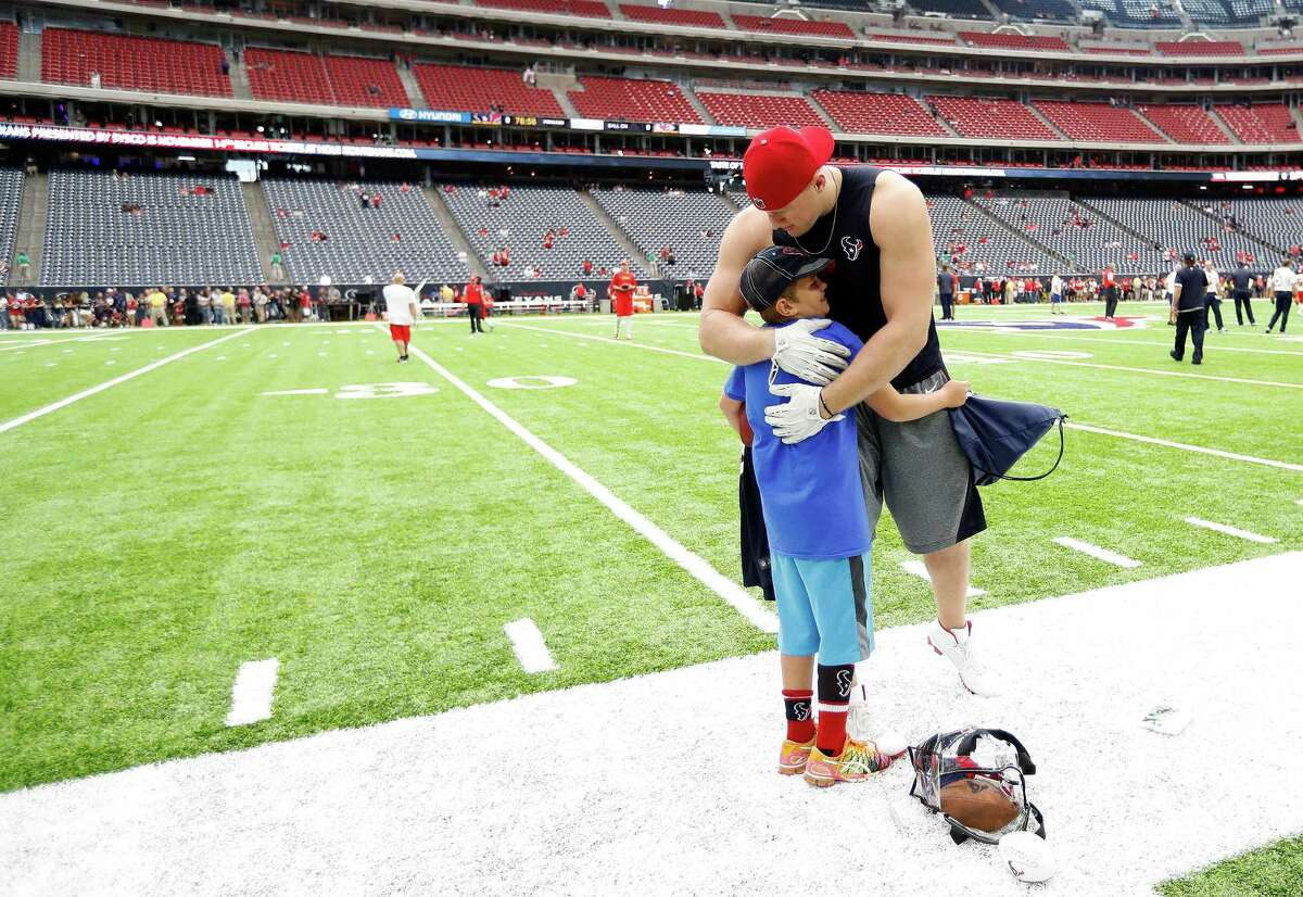 Houston Texans defensive end J.J. Watt gives Harrison Steiner, 10, of Phoenix, with Make-A-Wish a hug during warmups before the start of an NFL football game at NRG Stadium, Sunday, Sept. 18, 2016 in Houston.
