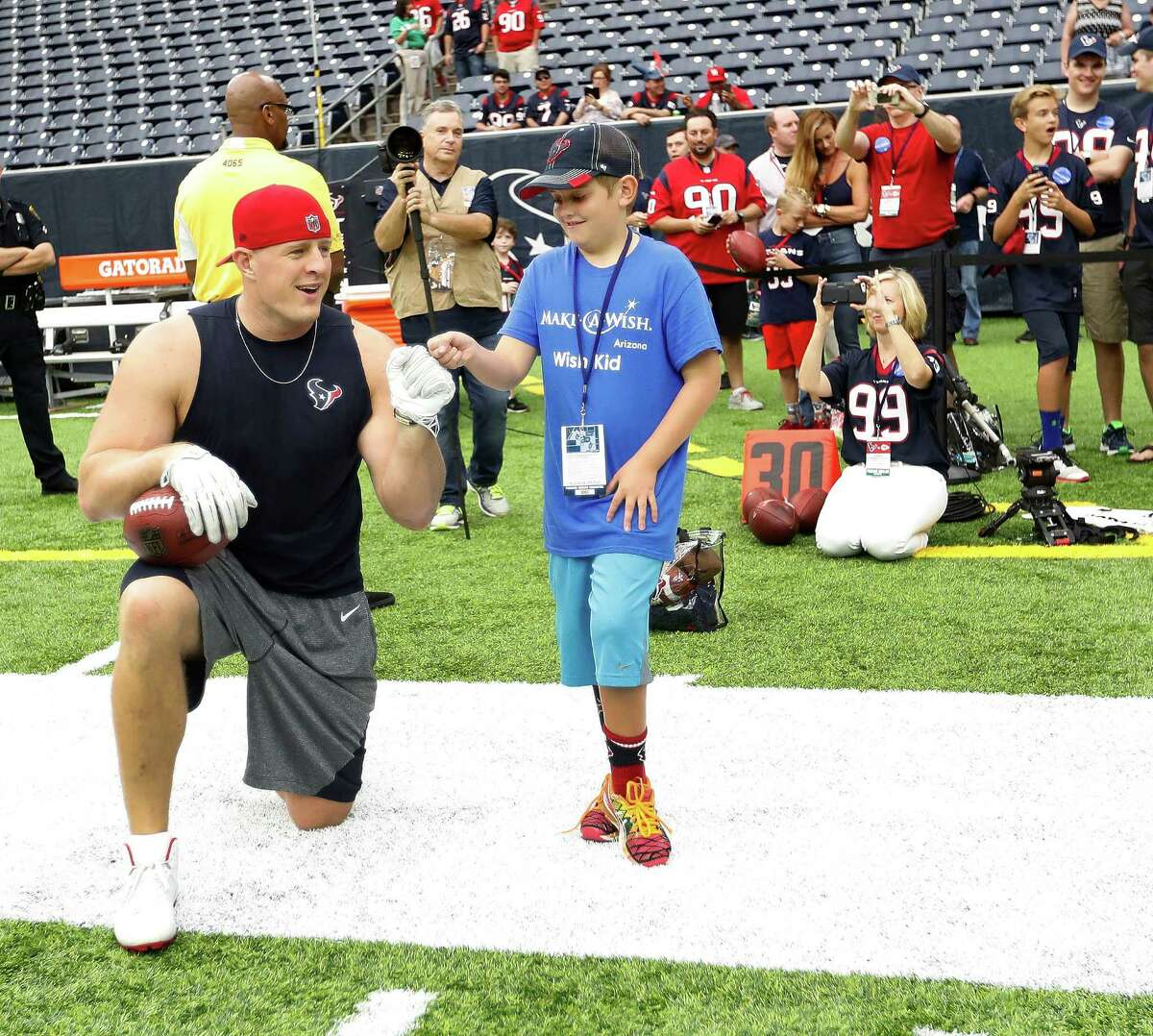 Houston Texans defensive end J.J. Watt chats with Harrison Steiner, 10, of Phoenix, with Make-A-Wish during warmups before the start of an NFL football game at NRG Stadium, Sunday, Sept. 18, 2016 in Houston.