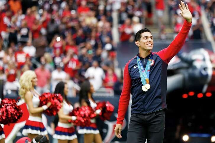 Olympic taekwondo gold medalist Steven Lopez leads the team onto the field before the first quarter of an NFL football game at NRG Stadium, Sunday, Sept. 18, 2016 in Houston.