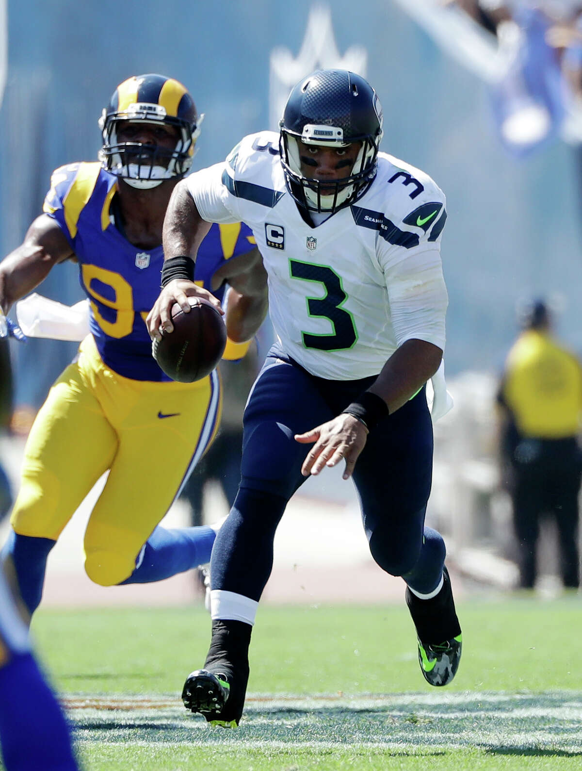 Seattle Seahawks quarterback Russell Wilson, right, runs the ball as Los Angeles Rams defensive end Robert Quinn pursues during the first half an NFL football game at Los Angeles Memorial Coliseum, Sunday, Sept. 18, 2016, in Los Angeles. (AP Photo/Jae Hong)