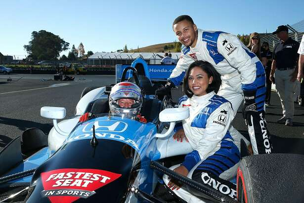 SONOMA, CA - SEPTEMBER 18: Grand Marshal for the GoPro Grand Prix of Sonoma Ayesha Curry and her husband Stephen Curry pose for a photo with Mario Andretti after taking a hot lap in a two-seater IndyCar at Sonoma Raceway on September 18, 2016 in Sonoma, California.  (Photo by Lachlan Cunningham/Getty Images)