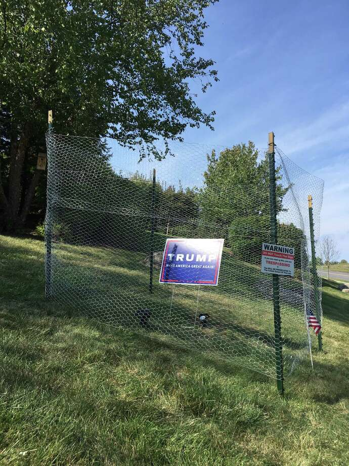 Chicken wire fencing surrounds a Donald Trump for president sign on Robert Marini's East Hills Boulevard lawn in Colonie, N.Y. The Capital Region home builder erected security measures in August to protect his show of political support but had to remove barbed wire fencing because it violated town zoning law. But after three thefts since — on top of the five that already occurred this summer — Marini put up the latest fencing to deter would-be sign snatchers.