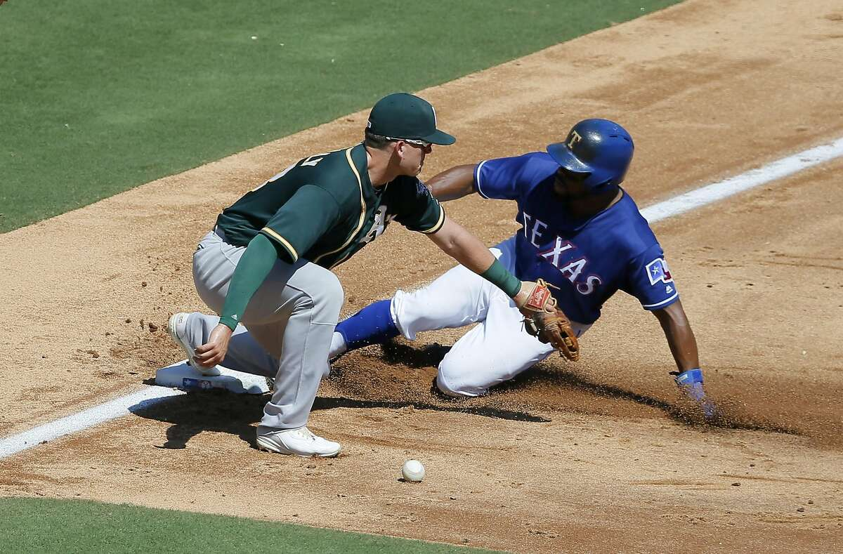 Oakland Athletics third baseman Ryon Healy, left, drops throw to the bag as Texas Rangers' Delino DeShields, right, slides in safely on the error by Healy in the third inning of a baseball game, Sunday, Sept. 18, 2016, in Arlington, Texas. (AP Photo/Tony Gutierrez)