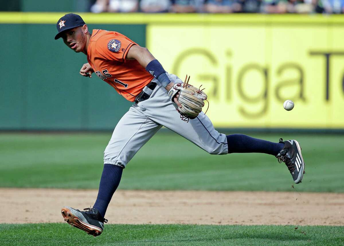 Houston Astros shortstop Carlos Correa misses grabbing a ground ball hit by Seattle Mariners' Norichika Aoki in the sixth inning of a baseball game, Sunday, Sept. 18, 2016, in Seattle. (AP Photo/Elaine Thompson)