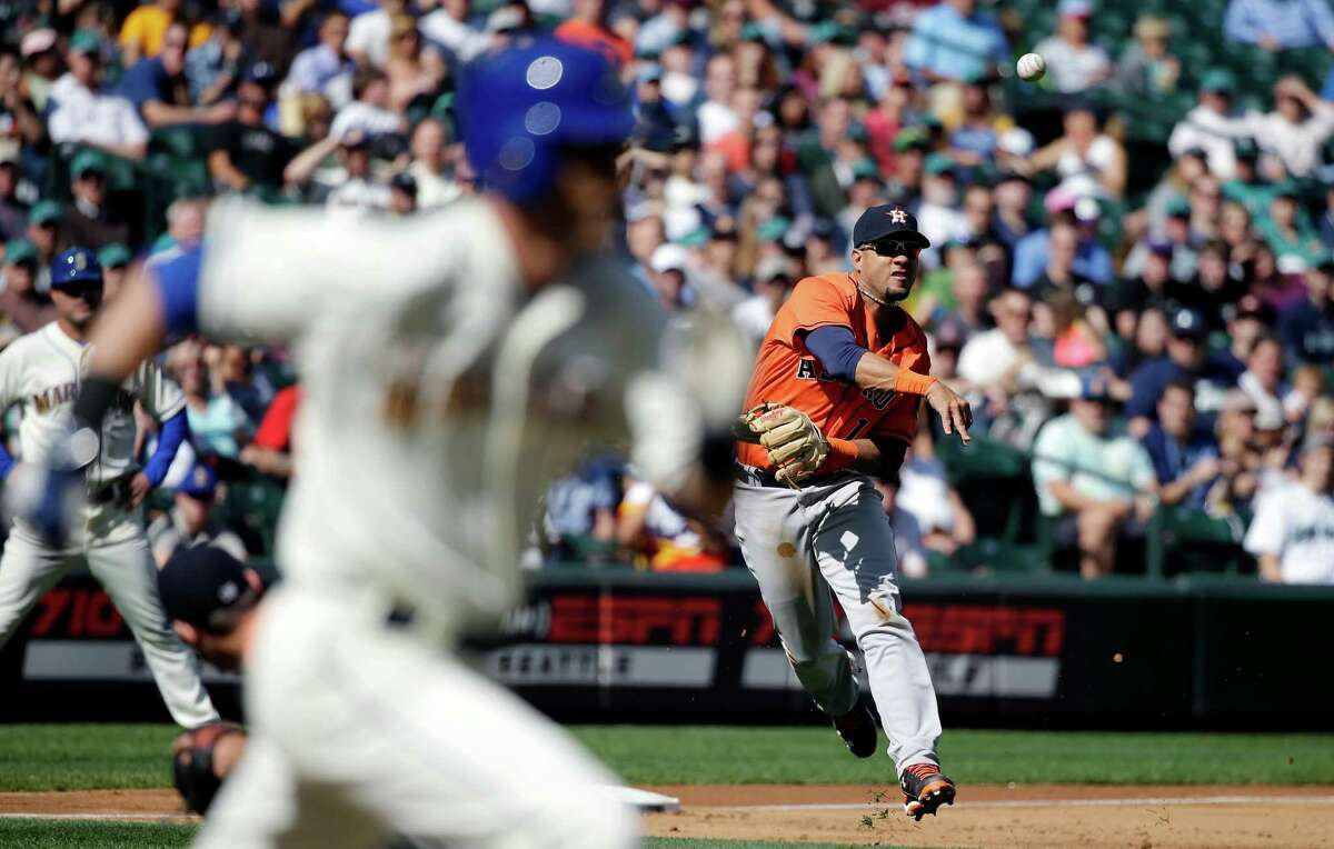 Houston Astros' Yulieski Gurriel, right, throws to first base after fielding a ground ball by Seattle Mariners' Shawn O'Malley, left, in the second inning of a baseball game Sunday, Sept. 18, 2016, in Seattle. Gurriel made the throw in time for the out. (AP Photo/Elaine Thompson)