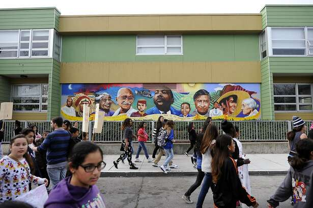 Student marchers walk past a mural with images of Martin Luther King Jr., Mahatma Gandhi and Cesar Chavez in front of MLK Middle School during a multi-school march honoring Dr. King's upcoming holiday, in San Francisco, CA, on Friday, January 16, 2015.