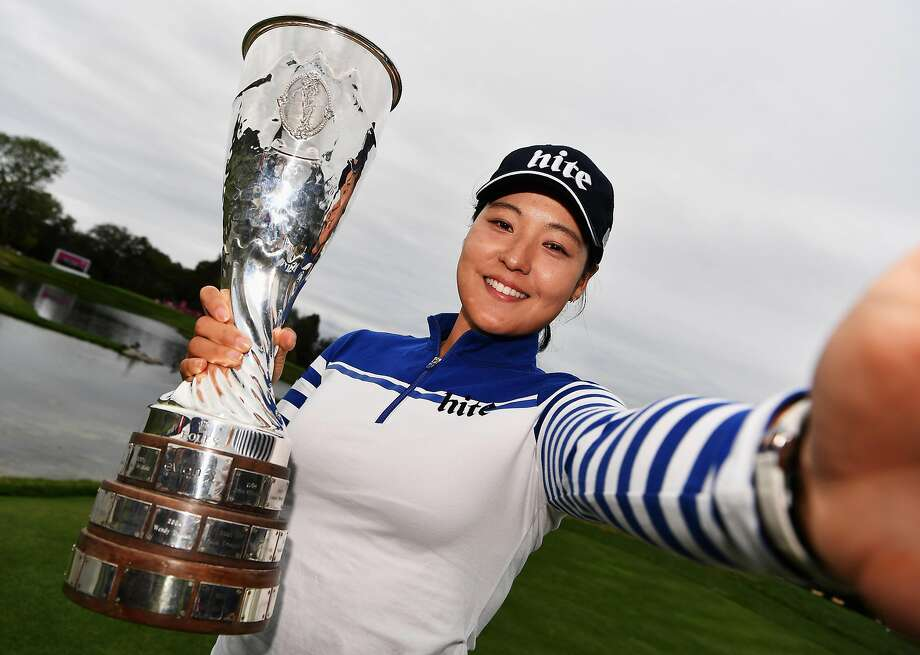 In Gee Chun takes a selfie (actually, she simulates one while grabbing a photographer's camera) with the Evian trophy. Photo: Stuart Franklin, Getty Images