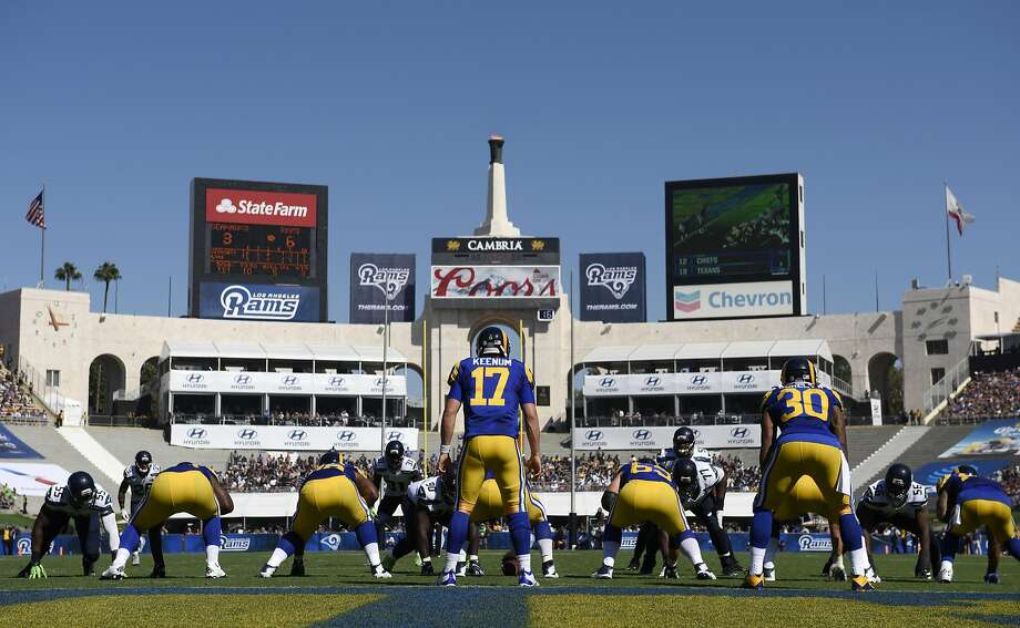 Rams QB Case Keenum (17) runs a play under the watchful gaze of the Olympic Cauldron at Los Angeles Memorial Coliseum. Photo: Kelvin Kuo, Associated Press