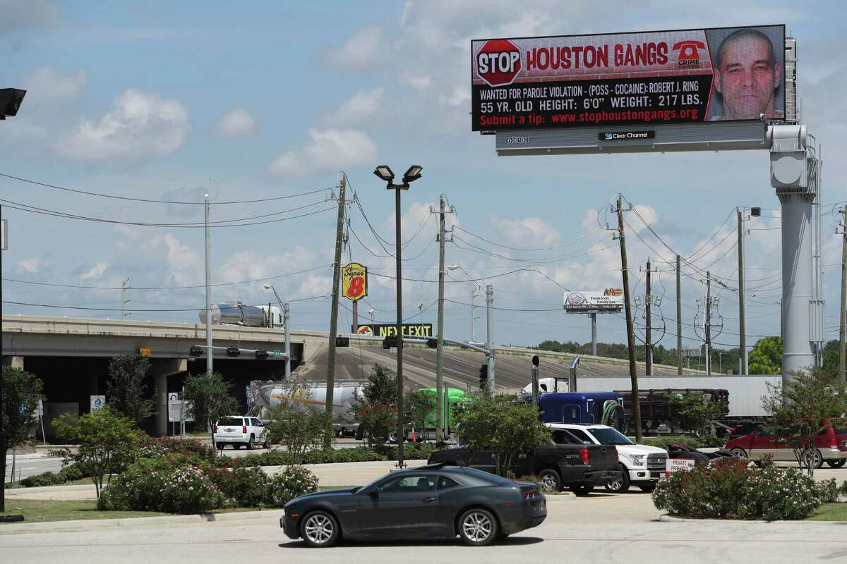 A large digital billboard shows a wanted poster for Aryan Circle member Robert Ring, who is part of the Houston's Most Wanted Gang Fugitive program.