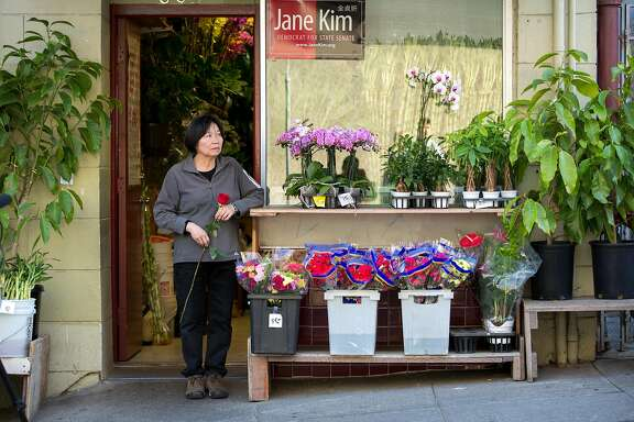 Sandy Weng outside her flower shop, next to the home of Rose Pak, where she died at her Chinatown apartment, Sunday, Sept. 18, 2016 in San Francisco, Calif. Wend said she is going to place the red rose in her hands outside Pak's home, once the crowd disperses.