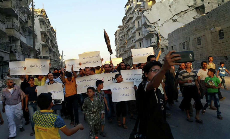 FILE - In this Sept. 13, 2016 file photo provided by Modar Shekho, activists in Syria's besieged Aleppo protest against the United Nations for what they say is its failure to lift the siege off their rebel-held area, in Aleppo, Syria. Residents in the rebel-held districts of Aleppo have a reprieve from the incessant bombings by Syrian government warplanes and the promise of an end to the crippling siege that has left produce stalls bare. (Modar Shekho via AP, File) ORG XMIT: HAS103 Photo: Modar Shekho / Modar Shekho