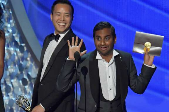 LOS ANGELES, CA - SEPTEMBER 18:  Writer/producers Alan Yang (L) and Aziz Ansari accept the Outstanding Writing for a Comedy Series award for the 'Master of None' episode 'Parents' onstage during the 68th Annual Primetime Emmy Awards at Microsoft Theater on September 18, 2016 in Los Angeles, California.  (Photo by Lester Cohen/WireImage)