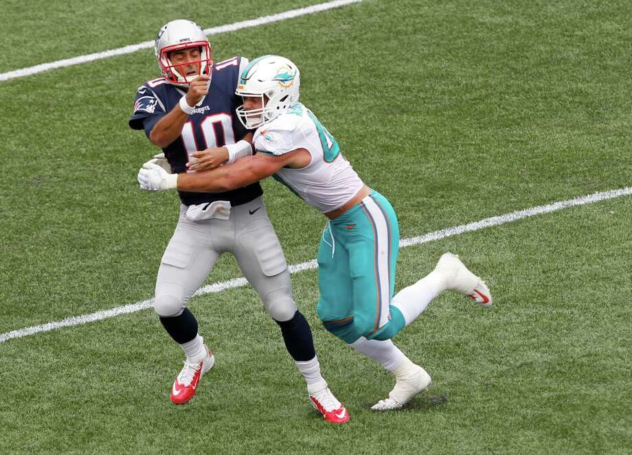 Miami Dolphins linebacker Kiko Alonso, right, hits New England Patriots quarterback Jimmy Garoppolo (10) after he threw a pass during the first half of an NFL football game Sunday, Sept. 18, 2016, in Foxborough, Mass. Garoppolo was injured on the play and did not return to the game. (AP Photo/Stew Milne) ORG XMIT: FBO133 Photo: Stew Milne / FR56276 AP