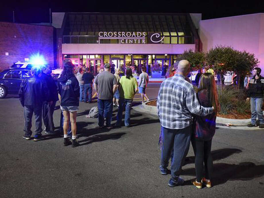 People stand near the entrance on the north side of Crossroads Center mall between Macy's and Target as officials investigate a reported multiple stabbing incident, Saturday, Sept. 17, 2016, in St. Cloud, Minn. Police said multiple people were injured at the St. Cloud shopping mall on Saturday evening in an attack possibly involving both shooting and stabbing. The suspect is believed to be dead, St. Cloud Police Sgt. Jason Burke told the St. Cloud Times. (Dave Schwarz/St. Cloud Times via AP) ORG XMIT: MNCLO300 Photo: Dave Schwarz / St. Cloud Times