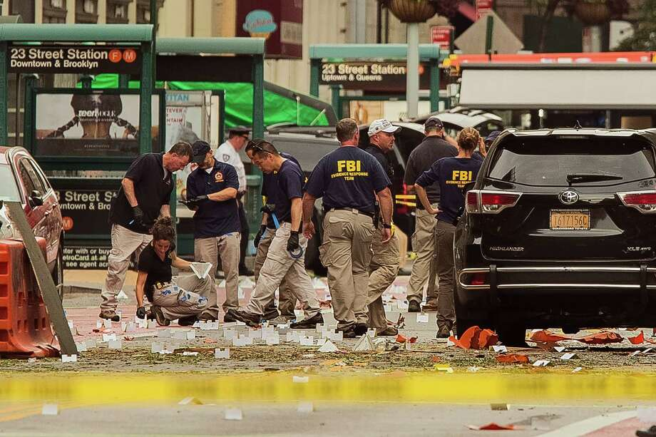 Members of the Federal Bureau of Investigation (FBI) carry on investigations at the scene of Saturday's explosion on West 23rd Street and Sixth Avenue in Manhattan's Chelsea neighborhood, New York, Sunday, Sept. 18, 2016. An explosion rocked the block of West 23rd Street between Sixth and Seventh Avenues at 8:30 p.m. Saturday. Officials said more than two dozen people were injured. Most of the injuries were minor. (AP Photo/Andres Kudacki) ORG XMIT: NYAK101 Photo: Andres Kudacki / FR170905 AP