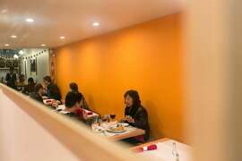 Customers dine in the narrow dining area of Cuisine of Nepal in S.F.