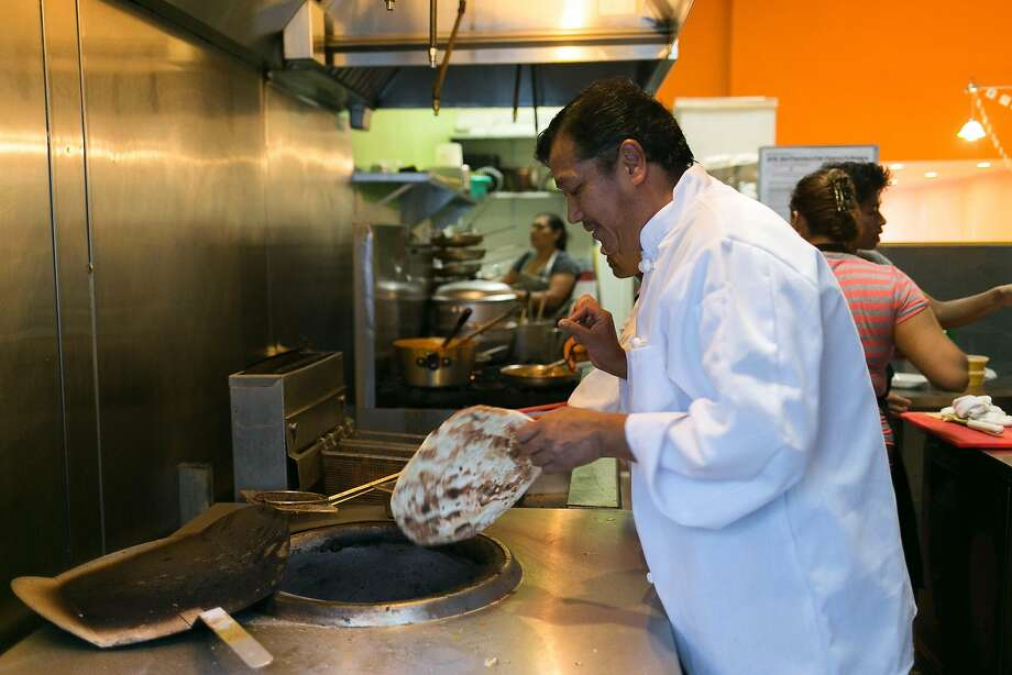 Prem Tamang pulls cooked naan from the oven at Cuisine of Nepal in S.F. Photo: Jen Fedrizzi, Special To The Chronicle
