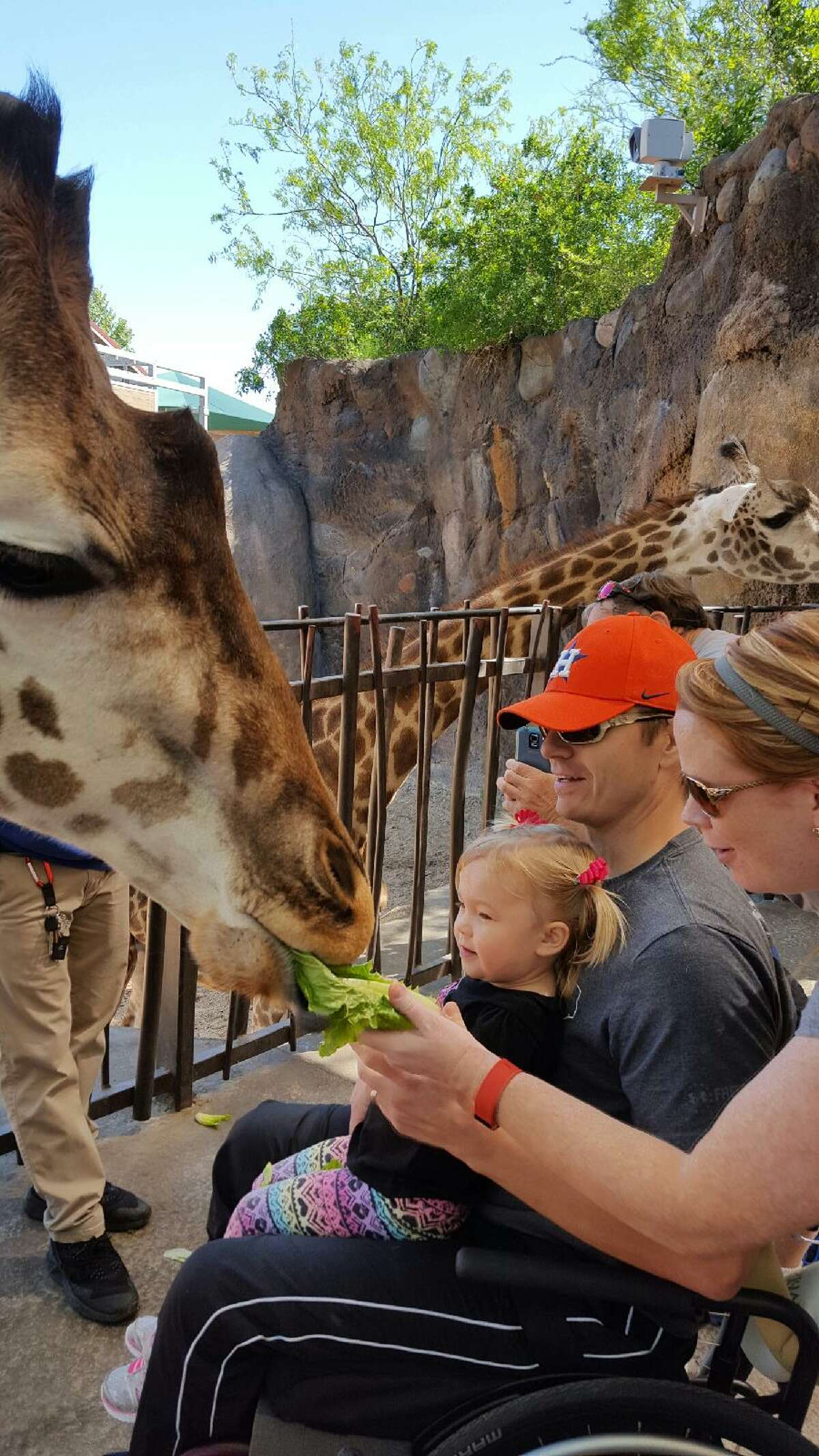 Warnke and his family feed the Houston Zoo's giraffes during a trip for patients put on by TIRR.