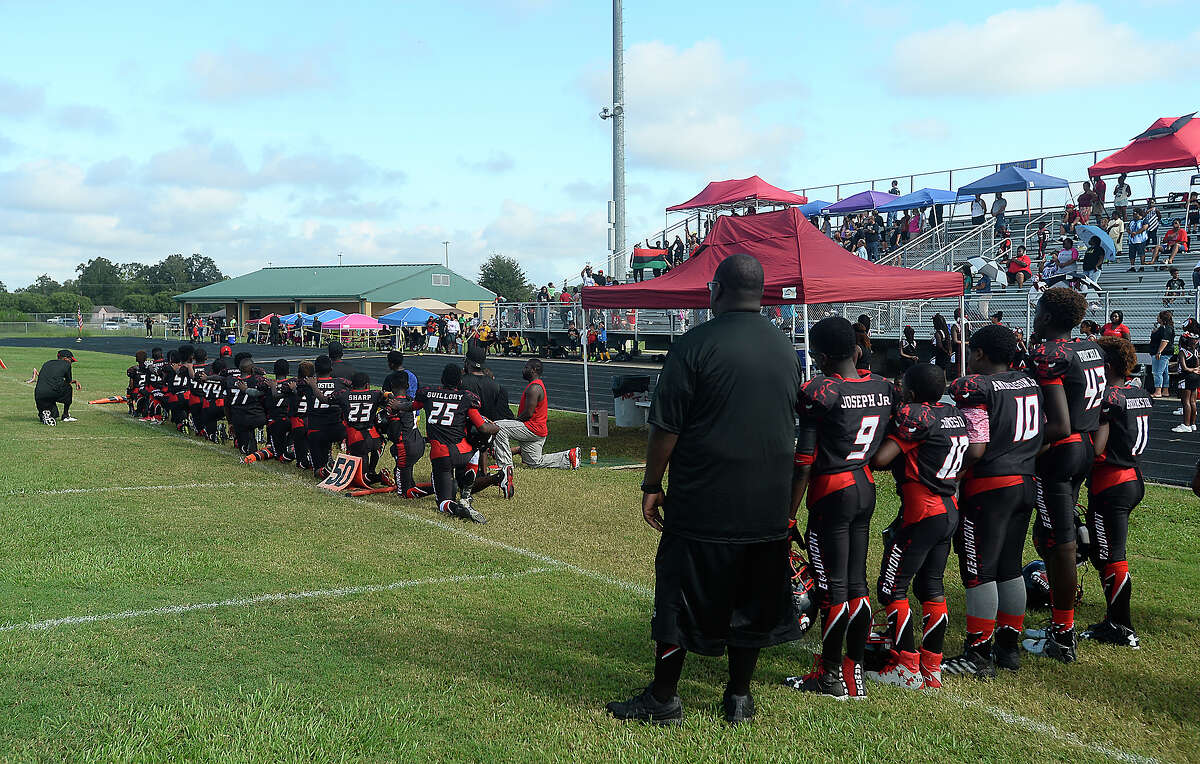 Some members of the Beaumont Bulls youth football team and coaches kneel while others stand during the playing of the National Anthem prior to their home game Saturday. The team has gotten national attention after choosing to kneel in protest of social injustice at their game last week. After receiving numerous negative comments, including threats of violence aimed at both the 11 - 12-year-old players as well as coaches and parents, questions arose as to whether their protest would continue, and what negative actions may be taken by board members of the Bulls football program. Ultimately, no action was immediately taken against those players who chose to kneel, and the game continued as scheduled. Photo taken Saturday, September 17, 2016 Kim Brent/The Enterprise