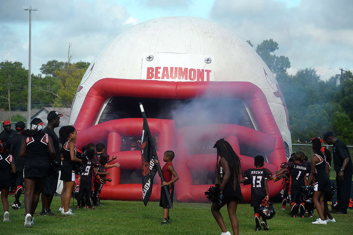 Members of the Beaumont Bulls get ready to make their entrance to face the Raiders from Alvin during Saturday's youth league game at Ozen High School. Some members of the Beaumont Bulls youth football team and coaches knelt while others stood during the playing of the National Anthem prior to their home game Saturday. The team has gotten national attention after choosing to kneel in protest of social injustice at their game last week. After receiving numerous negative comments, including threats of violence aimed at both the 11 - 12-year-old players as well as coaches and parents, questions arose as to whether their protest would continue, and what negative actions may be taken by board members of the Bulls football program. Ultimately, no action was immediately taken against those players who chose to kneel, and the game continued as scheduled. Photo taken Saturday, September 17, 2016 Kim Brent/The Enterprise