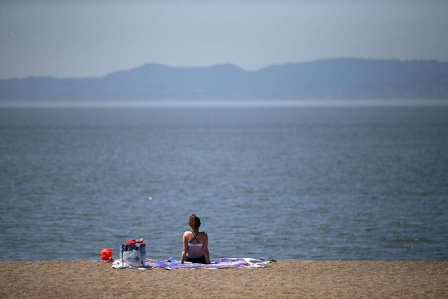 A sunbather sits on the beach at Alameda Beach on May 14, 2014 in Alameda, California. A heat wave in the Bay Area could lead to triple digits in parts of the region this weekend, forecasters said. Photo: Justin Sullivan, Getty Images
