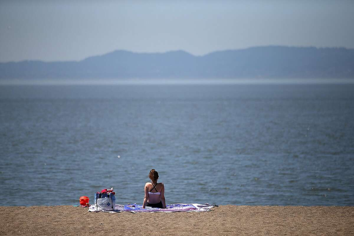 FILE: A sunbather sits on the beach at Alameda Beach on May 14, 2014 in Alameda, Calif. The National Weather Service on Saturday issued a coastal flood warning effective from 8 a.m. Sunday to 2 p.m. Monday.