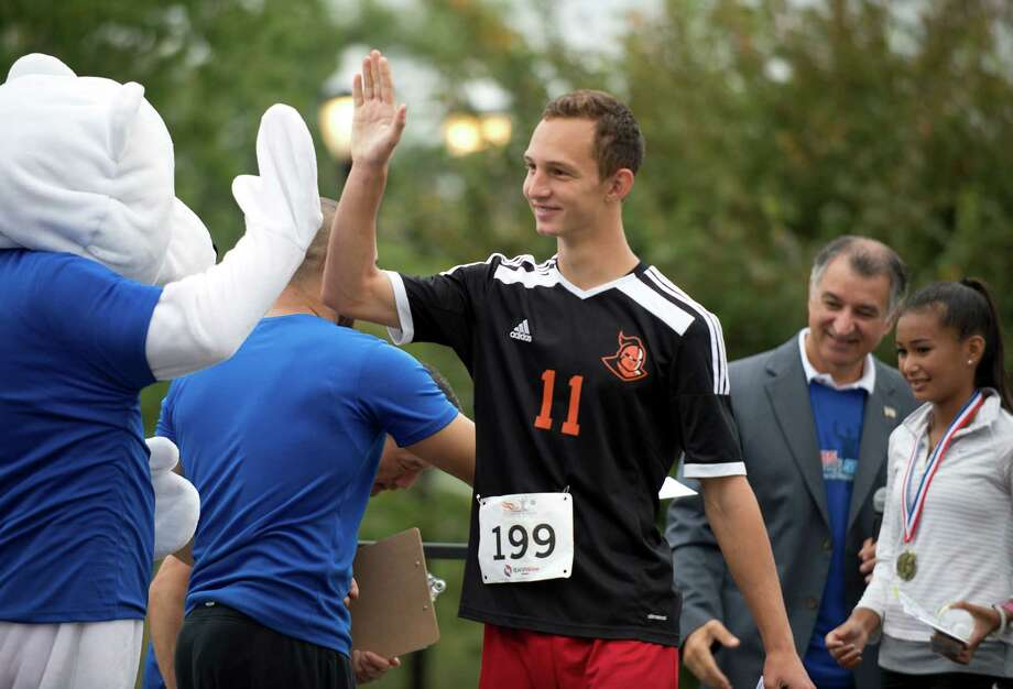 Uriy Yosypiv, 17 gets a high-five after coming in first overall in the fourth annual MarcUS for Change 5k Walk and Run, at Mill River Park in Stamford, Conn., on Sunday, September 18, 2016 Photo: Lindsay Perry / For Hearst Connecticut Media / Stamford Advocate Freelance