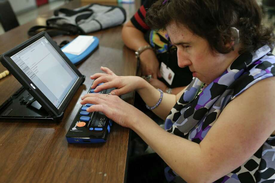Kim Shaffer uses an iPad with a braille device at HandsOn, a residential program for deaf-blind people on Sept. 13, 2016. The braille device allows Shaffer to read and send emails. The residential care nonprofit that helps deaf-blind folks and others almost had to close its doors until help arrived from the Kronkosky Charitable Foundation and another nonprofit, Mission Road Ministries. Photo: Jerry Lara /San Antonio Express-News / © 2016 San Antonio Express-News