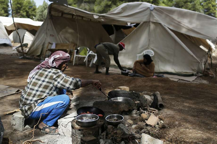 A Syrian cooks at the Ritsona refugee camp north of Athens. Scores of refugees fleeing war and destitution have surged into Europe in the past year. Photo: Petros Giannakouris, Associated Press